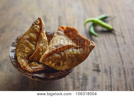 Popular indian street food - Punjabi Samosa in an earthen bowl with green chilies.