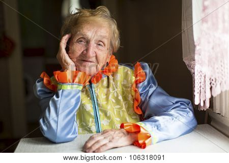 Old woman in ethnic slavic clothes sitting at a table in the house.