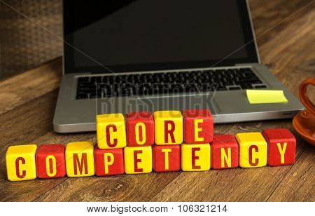 Core Competency written on a wooden cube in front of a laptop