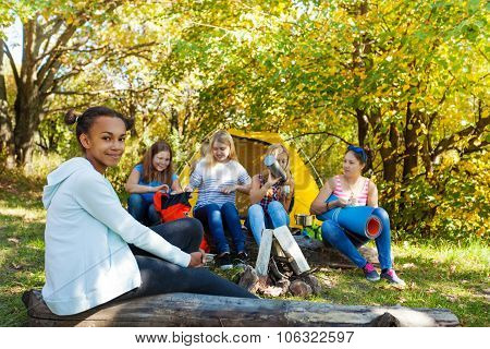 Smiling African girl sits on log with other girls