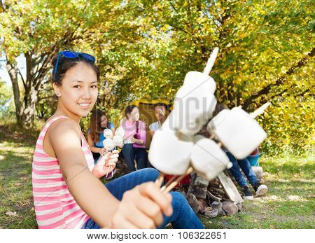 Smiling Asian girl holding sticks with marshmallow
