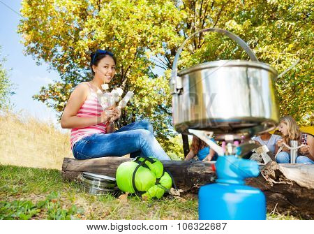 Girl holding marshmallow and pot close-up view