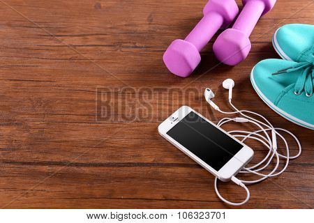 White cellphone with headphones and pink dumb bells and gumshoes on varnished wooden background