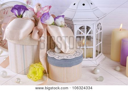 Beautiful composition of ballet shoes, candles, flowers and caskets, close up