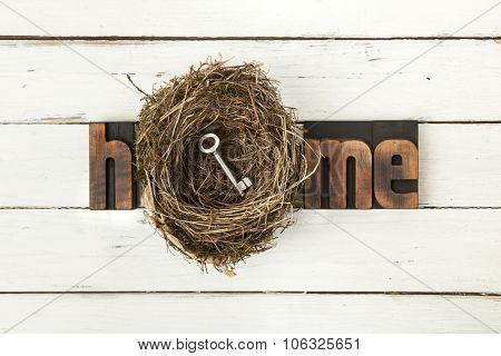 Home, word written with vintage letterpress printing blocks and bird nest containing a door key on rustic white painted wooden background