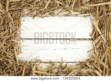 Rustic frame of hay on white painted wooden background