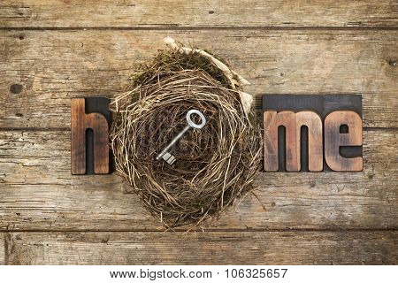 Home, word written with vintage letterpress printing blocks and bird nest containing a door key on rustic wooden background