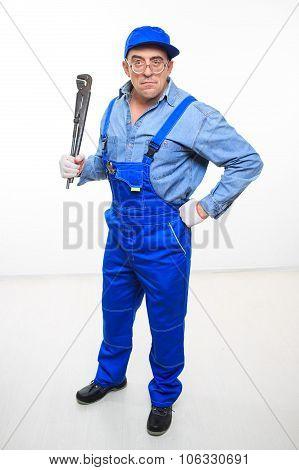 male mechanic holding monkey wrench on white background