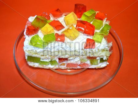 Appetizing Jelly cake on transparent dish on a red background