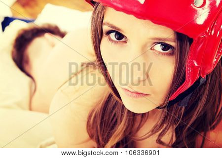 Afraid woman in protective helmet with her husband on bed.