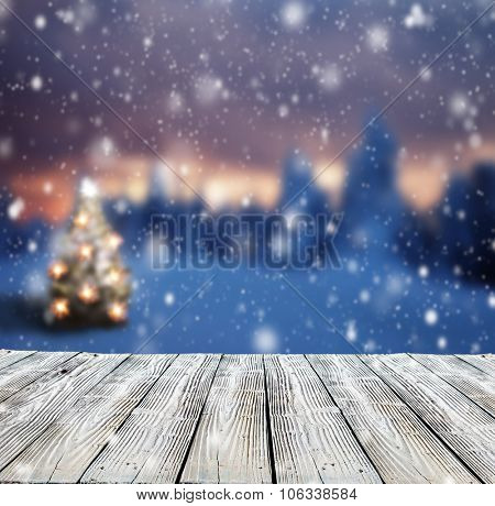 Winter background with mole and blur evening landscape. Empty wooden planks on foreground. Copyspace for text