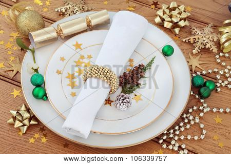 Christmas holiday dinner place setting with plates, napkin, bauble decorations, mistletoe over oak background.