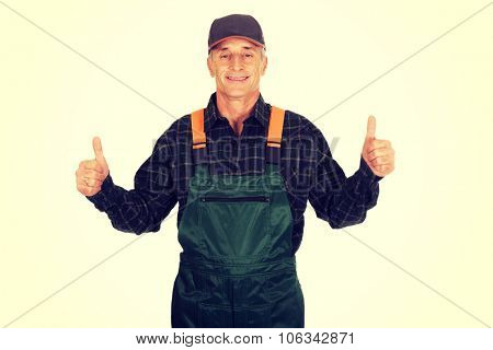 Experienced smiling gardener in uniform with thumbs up