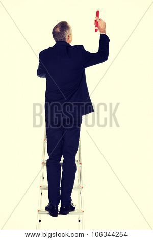 Mature businessman on a ladder with oversized pencil.