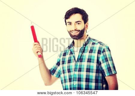 Young happy man holding oversized red pencil.