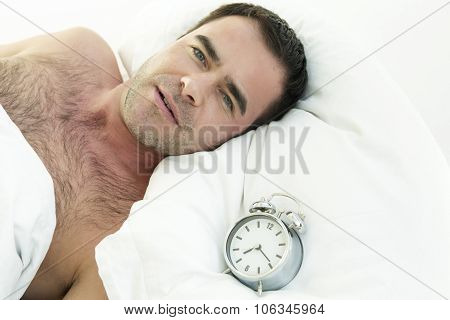 Man In Bed With Alarm Clock