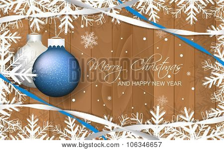 Christmas baubles and ribbons on wooden texture.