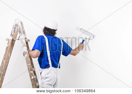 Painter Man At Work Climbing A Vintage Wooden Ladder And Painting With Paintroller