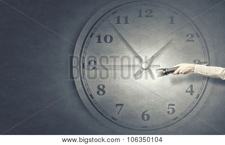 Hand of business person shine with flashlight on clock