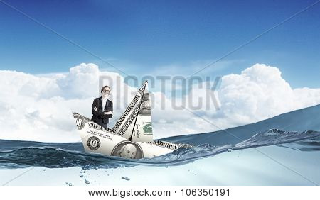 Businesswoman escapes from crisis on paper boat made of dollar banknote