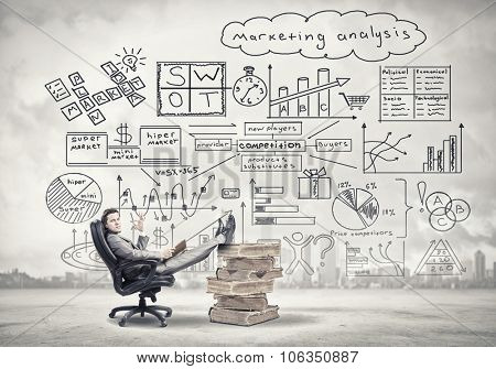 Young handsome businessman sitting in chair with his legs on pile of books and showing ok gesture