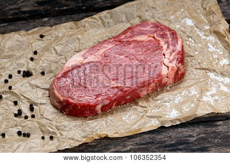 Raw Rib Eye Steak On Crumpled Paper, Pepper, Salt.