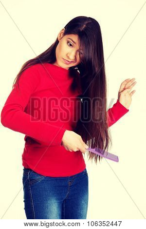 Painful woman combing her tangled hair.