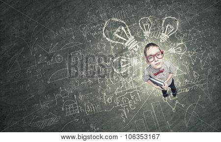 Top view of cute schoolboy in red glasses with books in hand