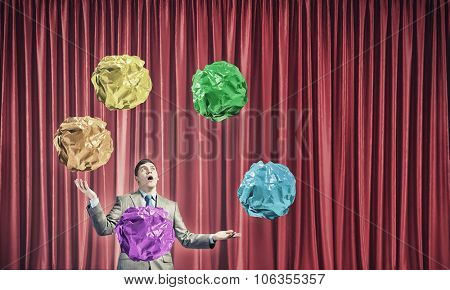 Businessman juggling with crumpled balls of colorful paper as creativity sign
