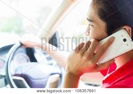 Asian young man telephoning with mobile phone or smartphone while driving car