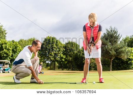 Senior woman and golf pro practicing their sport