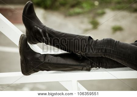 woman in black jeans and long leather boots sit on white metal fence in the city, day shot