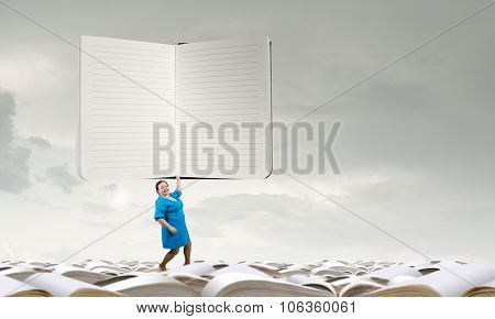 Middle aged stout woman in blue dress holding huge notepad