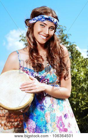 Happy hippie girl playing her drum outdoor.
