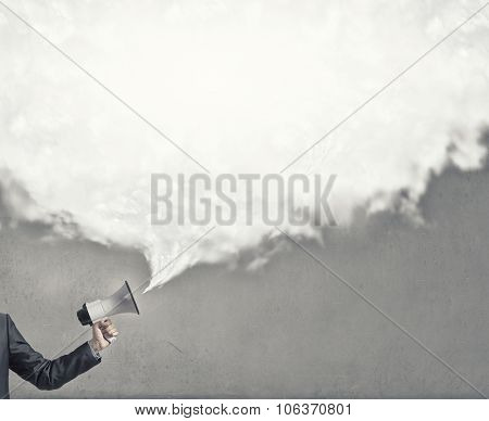 Hand holding megaphone and white speech blank cloud