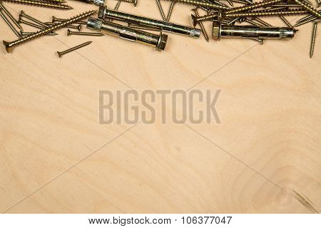 Golden screws on top with wood background