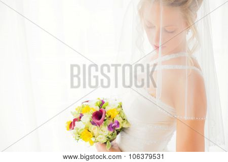Bride hiding behind veil with flowers in her hands