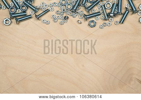 Boltas and nuts on top with wood background