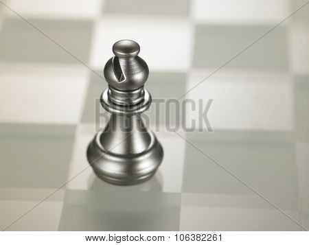 Silver color chess piece bishop on glass chess board