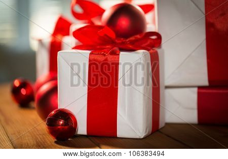 christmas, holidays, presents, new year and celebration concept - close up of gift boxes and red balls on wooden floor