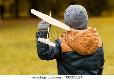 autumn, childhood, dream, leisure and people concept - happy little boy playing with wooden toy plane outdoors from back