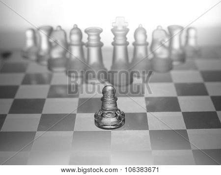 One pawn staying against full set of chess pieces.