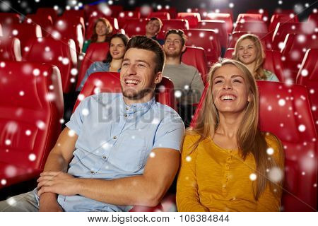 cinema, entertainment and people concept - happy couple watching comedy and laughing in movie theater over snowflakes