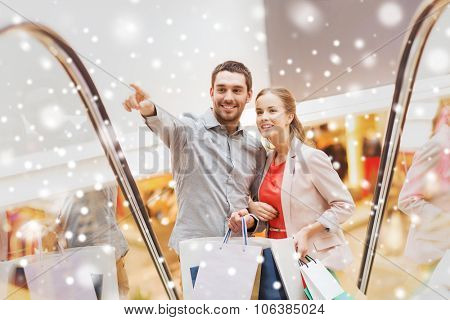 sale, consumerism and people concept - happy young couple with shopping bags rising on escalator and pointing finger and raising on escalator in mall with snow effect
