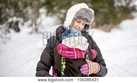 Happy Young Mother Carrying Her Baby In A Carrier