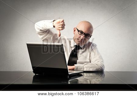 Disappointed businessman sitting in front of his pc