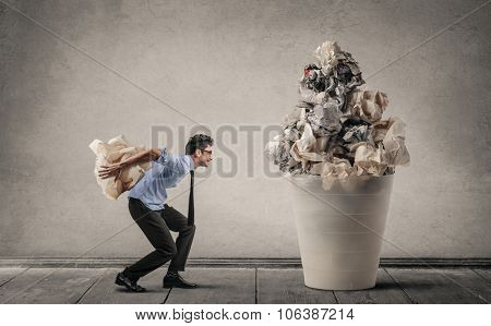 Employee trowing a piece of paper in a giant bin