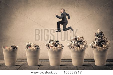 Businessman jumping over full trash bins