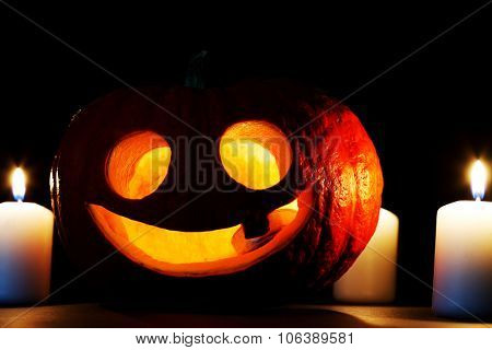 Halloween Jack O' Lantern pumpkin and candles on black background