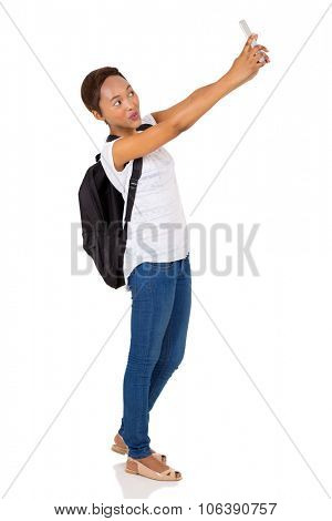 beautiful young african college girl taking selfie with smart phone camera on white background